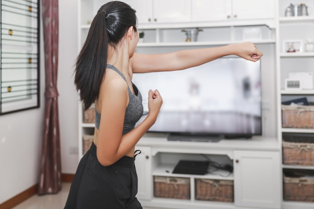 家庭の健康運動の概念、アジア人のフィット女性が家に滞在し、自宅のテレビでオンラインスポーツトレーニングクラスをトレーニング、covid-19発生の新しい正常な生活