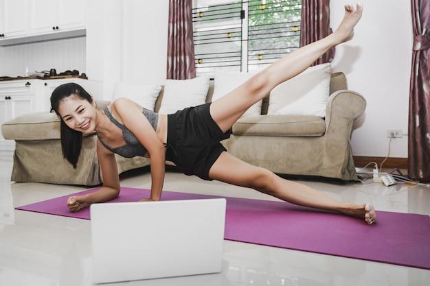Концепция домашних здоровых упражнений, азиатская подтянутая женщина остается дома с ноутбуком, тренируясь в онлайн-классе спортивных тренировок дома, новая нормальная жизнь вспышки covid-19