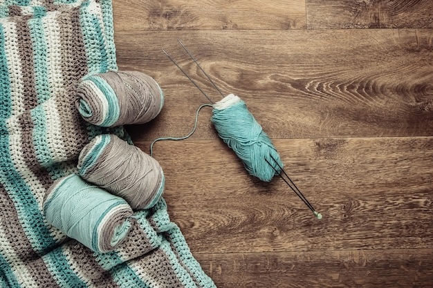 Home hobby. skeins of woolen threads, yarn, knitted product on the floor. top view