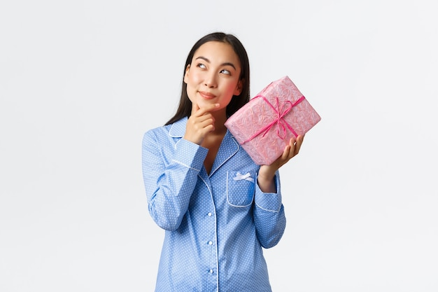 Home, holidays and lifestyle concept. intrigued happy birthday girl in blue pajama shaking box with gift to found out what inside, guessing the present and smiling curious, white background