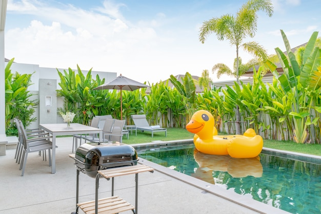 Home or house exterior design showing tropical pool villa with greenery garden, sun bed and floating duck