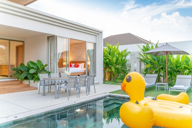 Home or house exterior design showing tropical pool villa with greenery garden, sun bed, umbrella, pool towels and floating duck