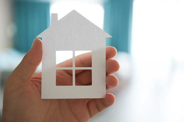 Home or house model on man hand in pastel color room background. investment wealthy freedom life concept
