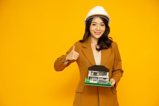 Домашний инспектор азиатская женщина или инженер показывает палец вверх в белом шлеме и держит модель дома на одну семью или отдельно стоящего дома, изолированную на желтом фоне