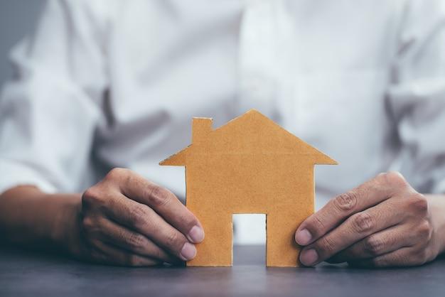 住宅保険と男性と家のモデルのジェスチャーの保護