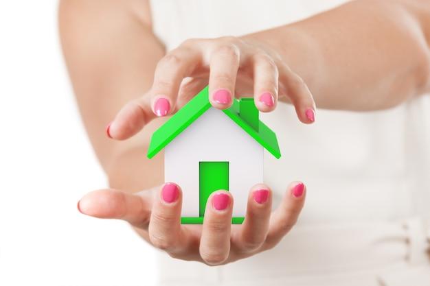 Концепция страхования жилья. две руки женщины защищая абстрактный зеленый дом на белом фоне.