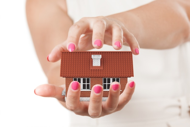 Home insurance concept. two woman hands protecting house on a white background.