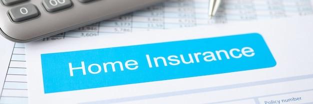 계산기 및 펜과 함께 주택 보험 계약은 테이블 부동산 보험에 놓여 있습니다.
