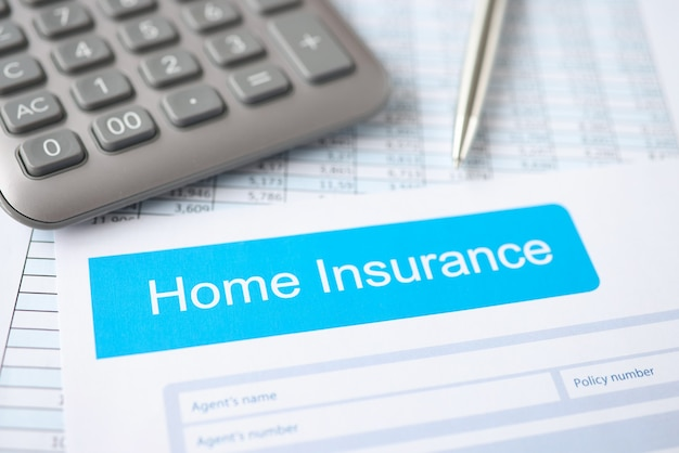 Home insurance contract along with calculator and pen lies on table