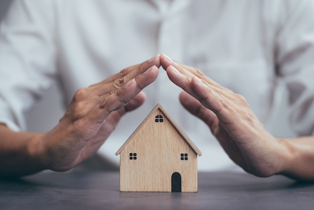 不動産のための住宅保険と人と家のモデルのジェスチャーを保護する