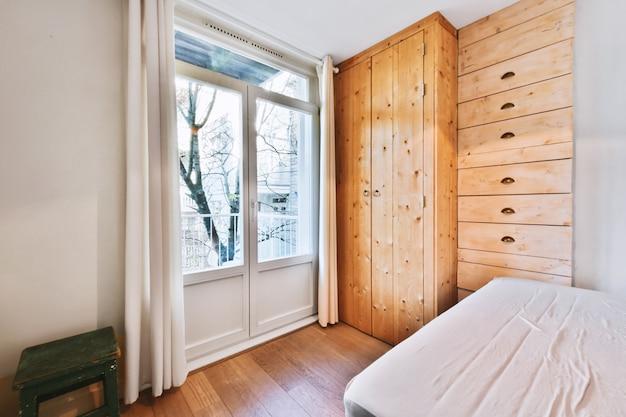 Домашний дизайн интерьера спальни с кроватью и деревянным шкафом в углу у окна в современной квартире