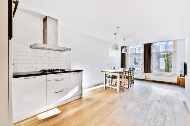 Домашний интерьер современной квартиры-лофта с открытой кухней в стиле минимализм и просторной обеденной зоной со столом и стульями.