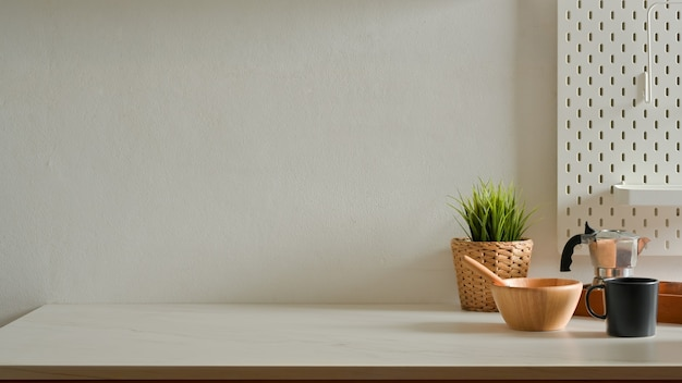 Home interior design with mixed bowl, coffee pot, mug, plant pot and copy space on kitchen table