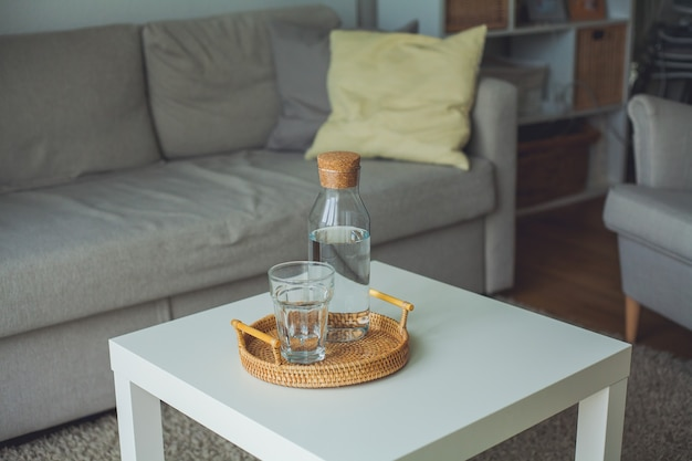 Home interior. a glass bottle with water, a glass, a rattan wicker tray on a coffee table. cozy.