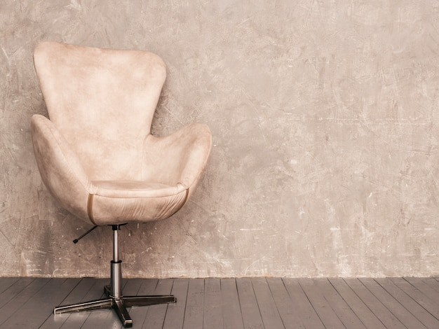 Home interior gray wall background with beige velvet armchair and wooden floor