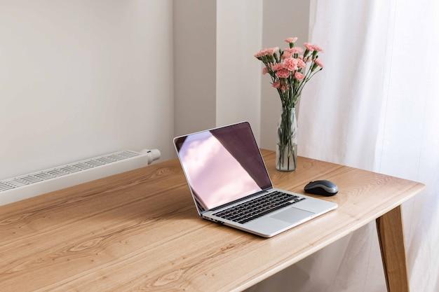 Домашний интерьер, домашнее рабочее место со столом и открытым ноутбуком крупным планом, цветы в вазе