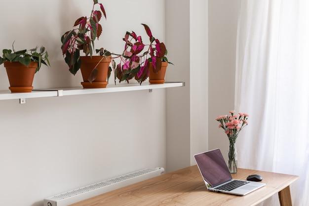 Домашний интерьер, домашнее рабочее место со столом и открытым ноутбуком, цветы в вазе