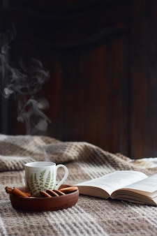 Home interior of living room. woolen blanket and a cup of tea with steam. breakfast on the couch in the morning sun. cozy autumn or winter concept. hyugge comfort