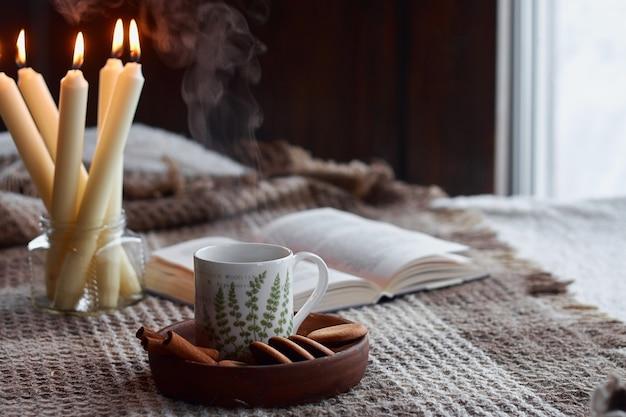 居間の家の内部。ウールの毛布とスチーム入りのお茶。朝の太陽の下でソファで朝食。居心地の良い秋または冬のコンセプト。ヒュッゲの快適さ