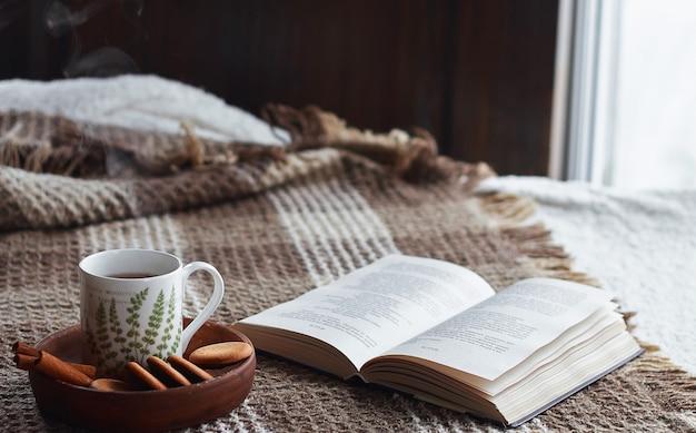 Домашний интерьер гостиной. шерстяное одеяло и чашка чая с паром. завтрак на диване под утренним солнцем. уютная осенняя или зимняя концепция. комфорт хюгге