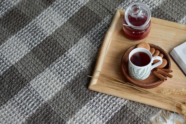 Домашний интерьер гостиной. шерстяное одеяло и чашка чая с паром. завтрак на диване под утренним солнцем. уютная осенняя или зимняя концепция. место для текста