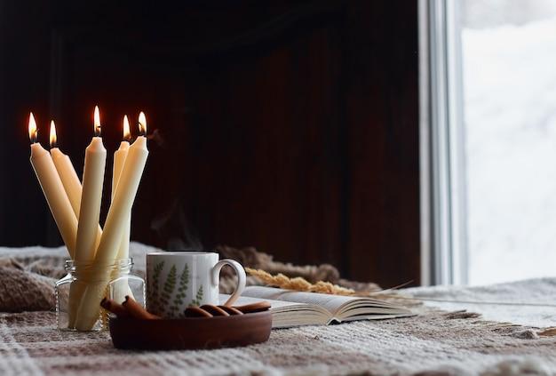 Домашний интерьер гостиной. шерстяное одеяло и чашка чая с паром. завтрак на диване под утренним солнцем. hygge комфорт