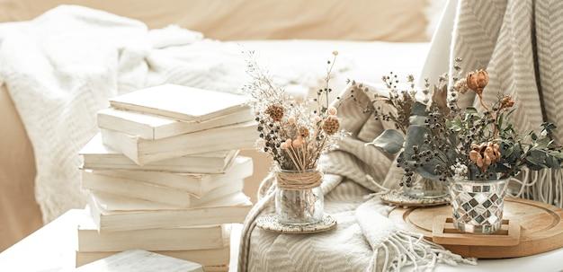 Interno di casa con libri e fiori secchi.