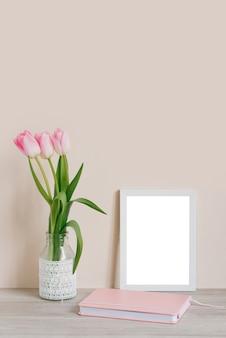 Домашний интерьер с элементами декора. макет с белой рамкой и розовыми тюльпанами в вазе и розовой записной книжкой на столе на светло-бежевом фоне