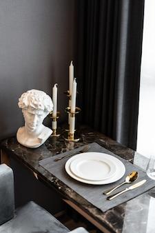 金のステンレス製の食器と大理石の上にカトラリーの設定でダイニングルームのテーブルの設定とホームインテリア。インテリア・デザイン