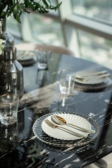 Home interior with dining room table setting with gold stainless tableware and cutlery setting on natural marble top