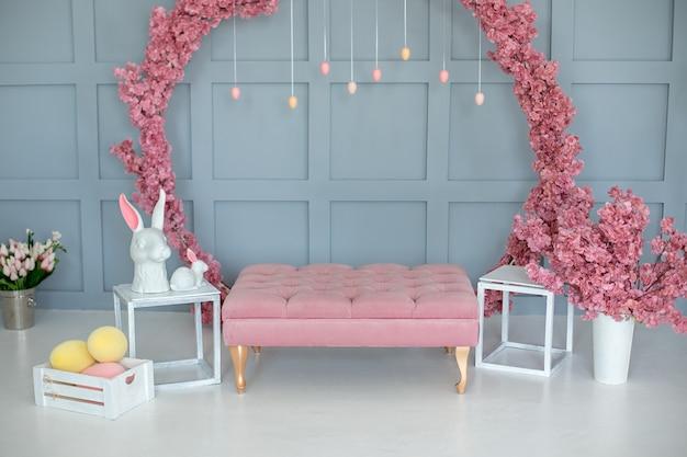 Домашний интерьер в пасхальном деко с розовым диваном и цветочным венком на голубом фоне