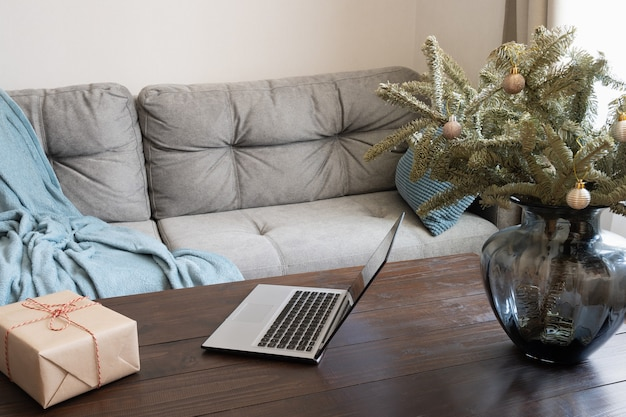 Home interior with laptop in living room with alternative christmas tree in vase. online shopping and booking. xmas.