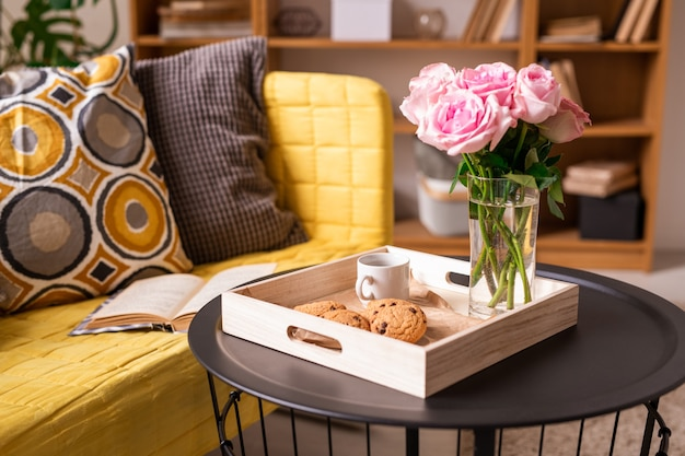 Домашний интерьер с подушками и открытой книгой на диване и столиком с печеньем, чашкой кофе и букетом розовых роз в деревянной коробке