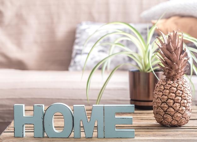 Interno di casa con ananas e lettere con la scritta home sul tavolo .il concetto di comfort domestico e creatività