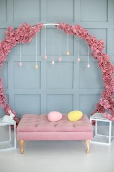 Домашний интерьер с розовым диваном большой венок сакуры на стене пасхальный декор гостиной