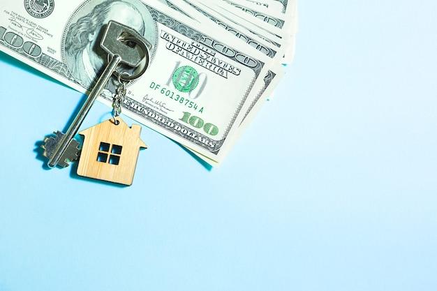 파란색 배경에 100달러 지폐 더미에 키체인이 있는 홈 키. 은행, 저축, 현금, 이사에서 아파트, 주택, 부동산, 비즈니스, 모기지 및 주택 대출 구매. 복사 공간 프리미엄 사진