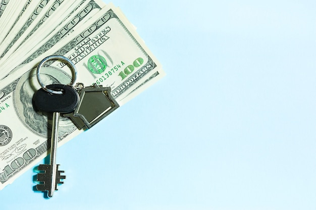 파란색 배경에 100달러 지폐 더미에 키체인이 있는 홈 키. 은행, 저축, 현금, 이사에서 아파트, 주택, 부동산, 비즈니스, 모기지 및 주택 대출 구매. 복사 공간