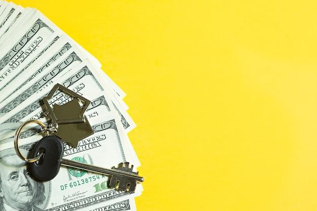 노란색 배경에 100달러 지폐 더미에 키체인이 있는 홈 키. 은행, 저축, 현금, 이사에서 아파트, 주택, 부동산, 비즈니스, 모기지 및 주택 대출 구매. 복사 공간