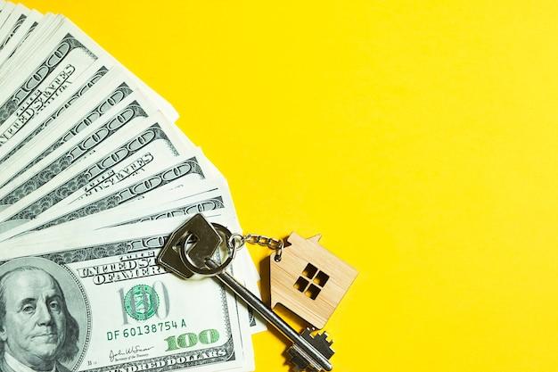 노란색 배경에 100달러 지폐 더미에 키체인이 있는 홈 키. 은행, 저축, 현금, 이사에서 아파트, 주택, 부동산, 비즈니스, 모기지 및 주택 대출 구매. 복사 공간 프리미엄 사진