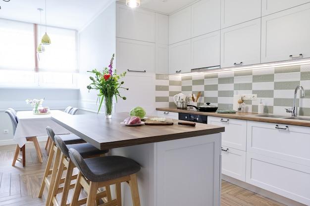 Интерьер домашней кухни, кухонная мебель, процесс приготовления пищи. пищевое мясо, лук, капуста на столешнице острова