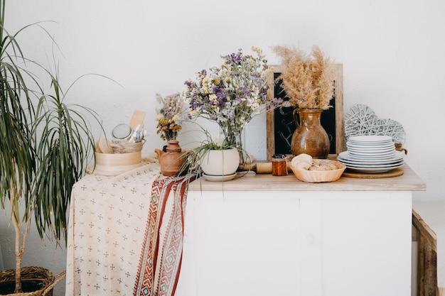 테이블, 점토, 나무 기구, 꽃이 있는 아파트의 소박한 실내 장식