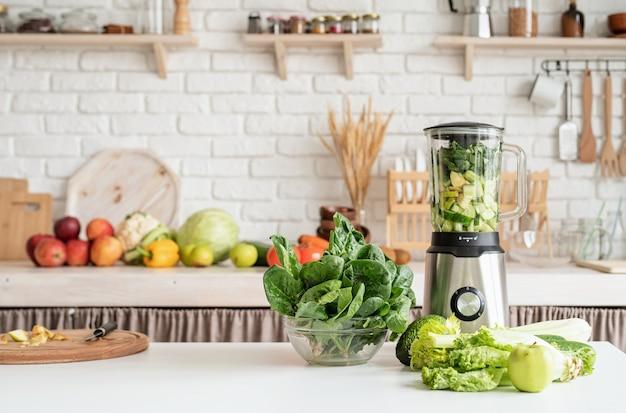 녹색 채소와 믹서기가있는 테이블이있는 홈 주방