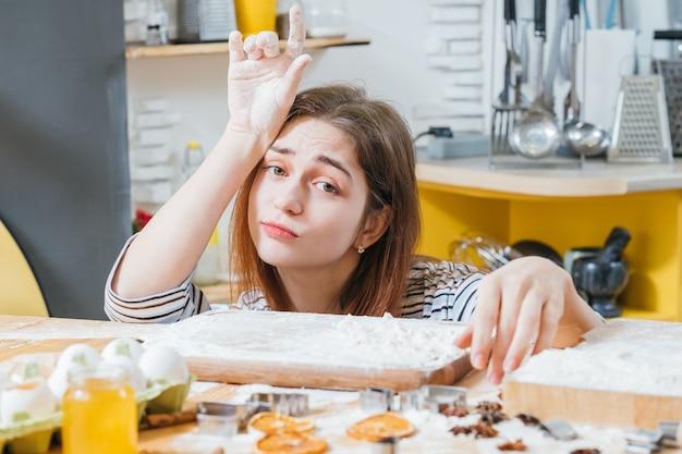 ホームレジャー。キッチンに座って、小麦粉で覆われた手、ビスケットの準備ができているのを待っている疲れた女性の肖像画。