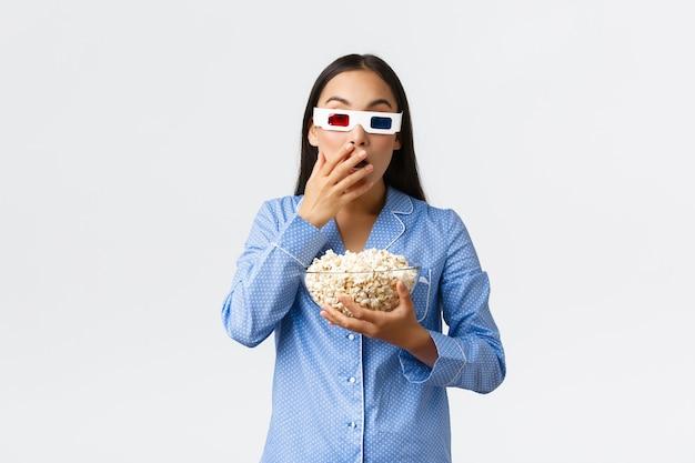 ホームレジャー、寝坊、眠りのパーティーのコンセプト。パジャマと3dメガネで驚いて驚いた若いアジアの女の子、テレビで激しい瞬間を見て、映画の夜にポップコーンを食べる
