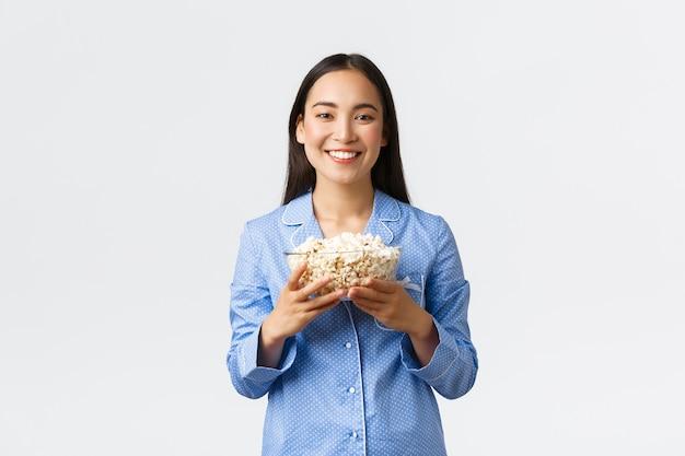 홈 레저, 수면 및 파자마 파티 개념. 웃고 있는 아시아 소녀는 주말에 팝콘을 들고 침대에서 즐기고 잠옷을 입고 영화를 보고 흰색 배경에 서 있습니다.