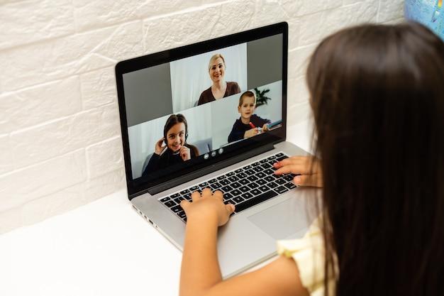 Концепция дома, досуга, технологий и интернета - маленькая студентка с портативным компьютером дома, маленькая девочка использует видеочат