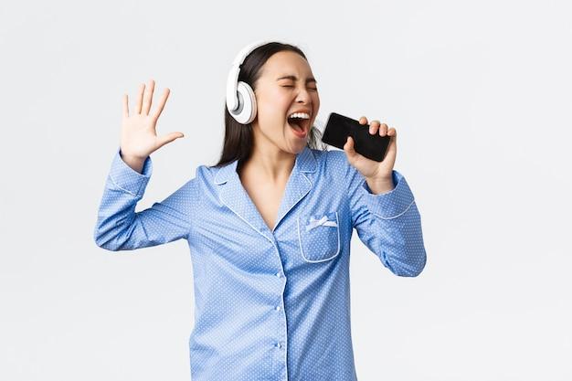 홈 레저, 주말 및 라이프 스타일 개념. 파자마를 입은 흥분되고 평온한 아시아 소녀, 스마트폰에서 노래방 앱을 재생하고, 헤드폰을 끼고 휴대폰에 노래를 부르고, 흰색 배경.