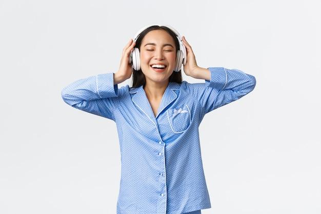 홈 레저, 주말 및 라이프 스타일 개념. 새 이어폰으로 멋진 음질을 즐기고 잠옷을 입고 춤을 추고 음악을 들으며 잠옷을 입은 행복한 아시아 여성.