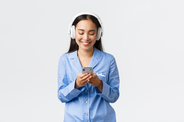 Домашний досуг, выходные и концепция образа жизни. улыбающаяся симпатичная азиатская женщина в синей пижаме и наушниках, слушает музыку, отправляет текстовые сообщения или смотрит видео на мобильном телефоне, улыбается на дисплее
