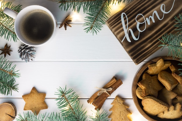 Home lettering burnt wood sign, gingerbread cookie, christmas tree branches, cup of coffee, cinnamon sticks on white surface. flat lay.